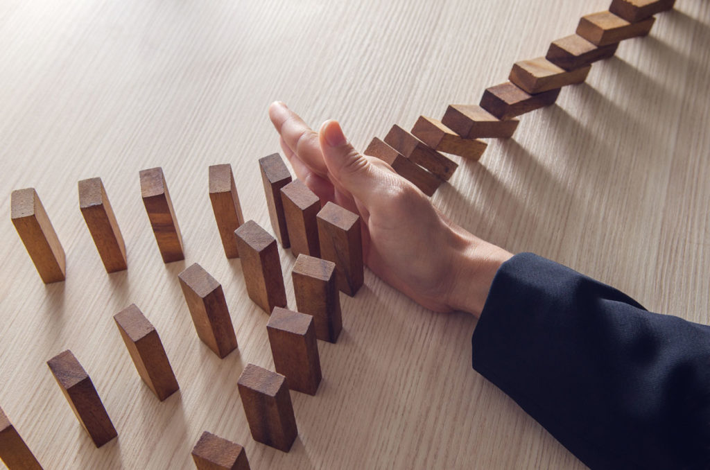 a line of dominos being blocked by a persons right hand